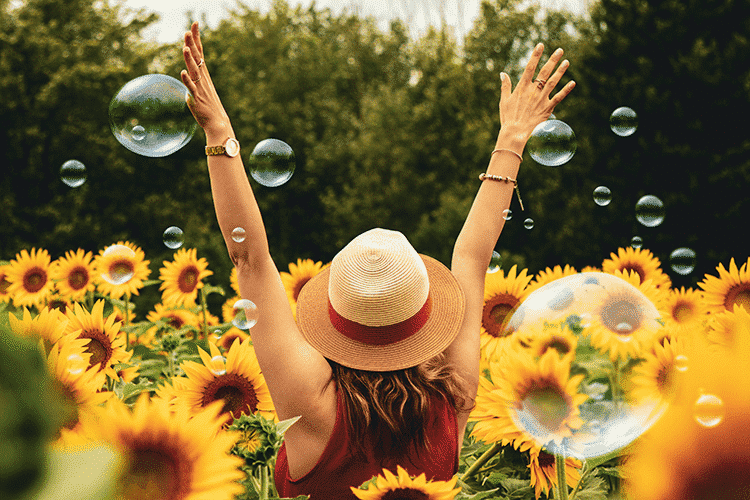 Happiest-Cities-woman-sunflowers-hat-bubbles