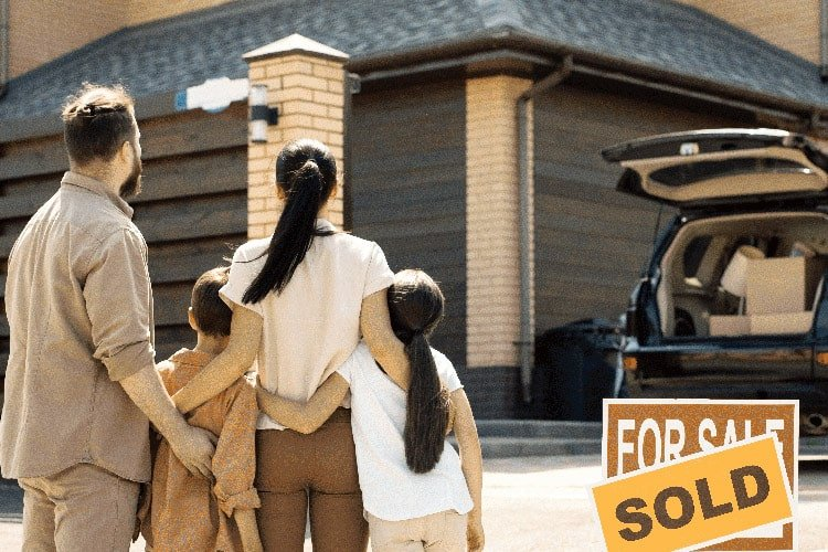 family in front of a new house with sold sign